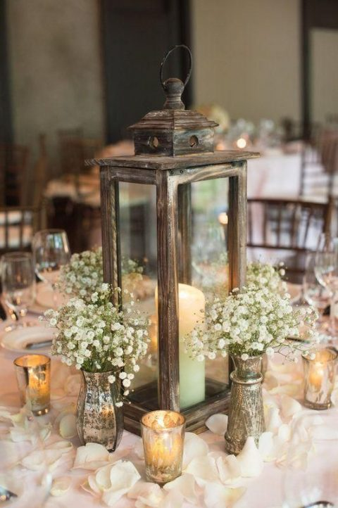 a wooden candle lantern surrounded with baby's breath and candles