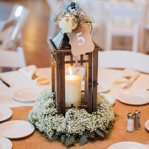 a wooden candle lantern with a bloom and table number on top and baby's breath around