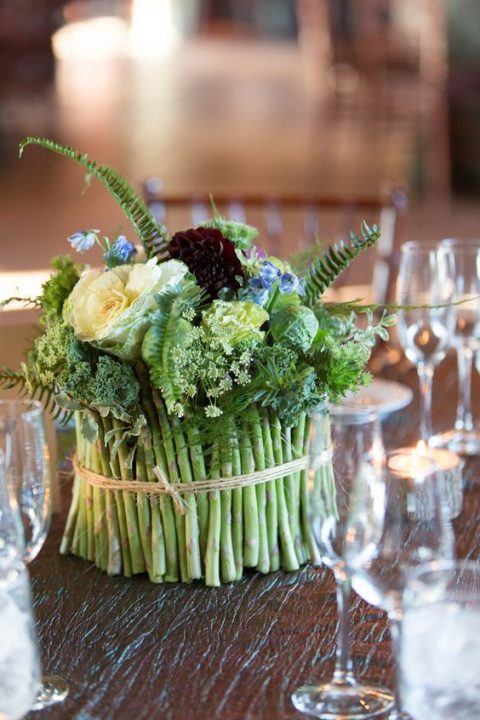 an asparagus centerpiece with fern, blooms and herbs for a fall celebration