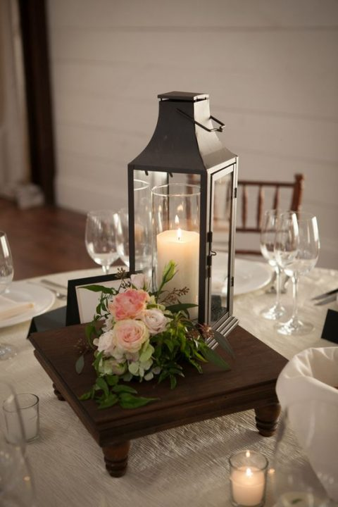 an elegant black candle lantern, pink roses and a wooden stand