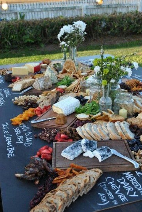 an outdoor cheese station on a large chalkboard to name every sort of cheese
