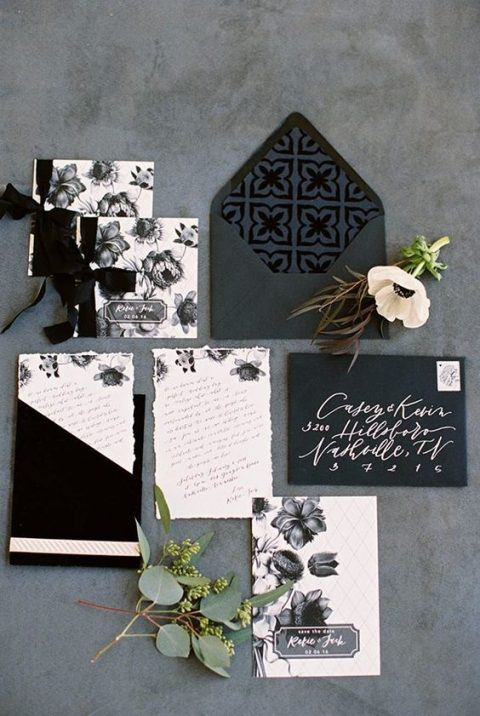 black and white wedding stationery with floral prints and calligraphy