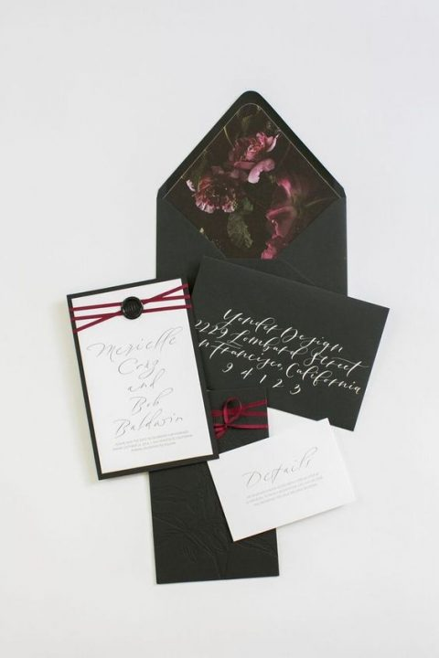 black textured stationery with plum-colored floral lining and plum ribbon