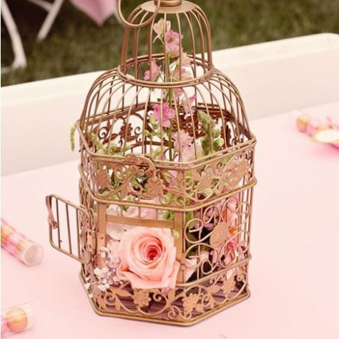 gilded bird cage with pink florals inside