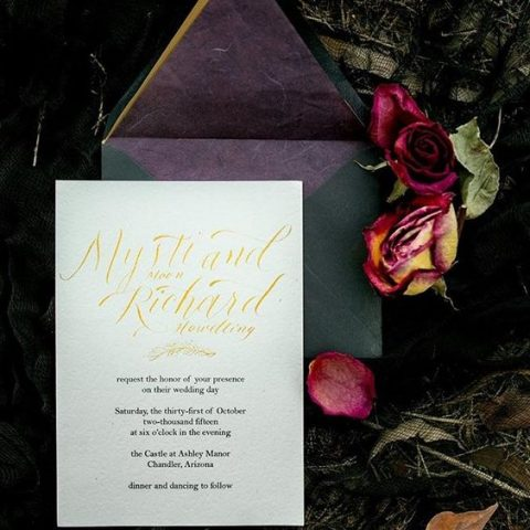 green and purple wedding envelopes with neutral invites and gold calligraphy