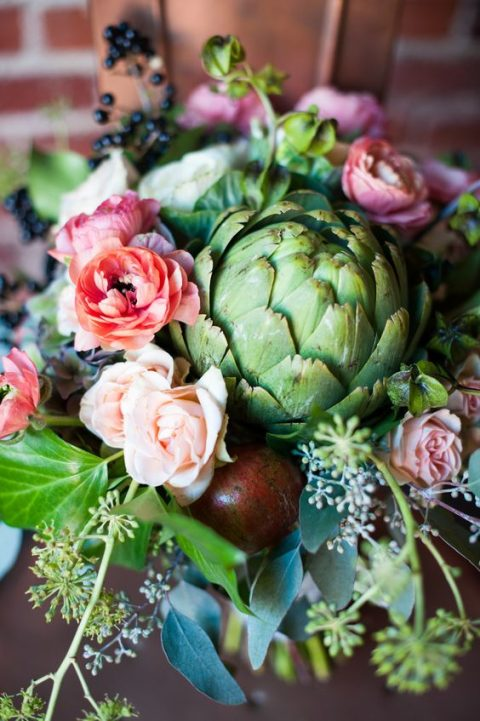 pink and blush flowers, an artichoke and herbs for a unique wedding centerpiece