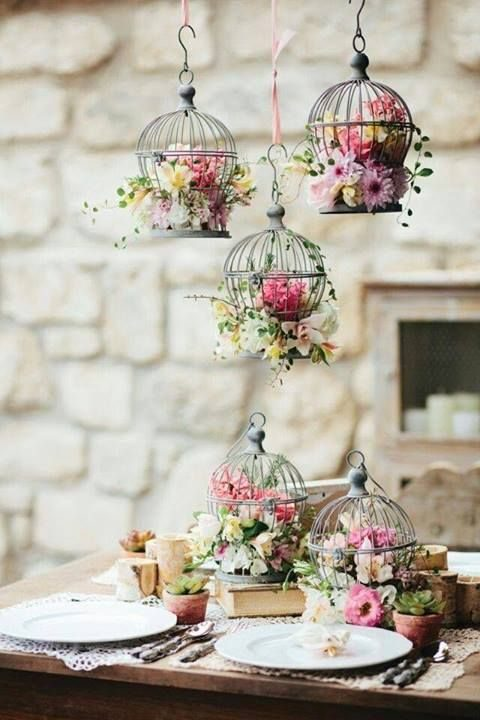 small bird cages with bold floral arrangements on the table and hung over it