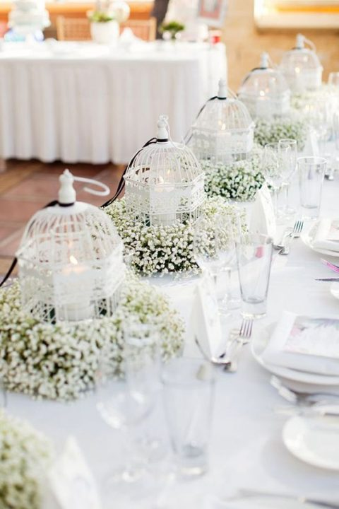 white bird cages with candles inside and baby's breath