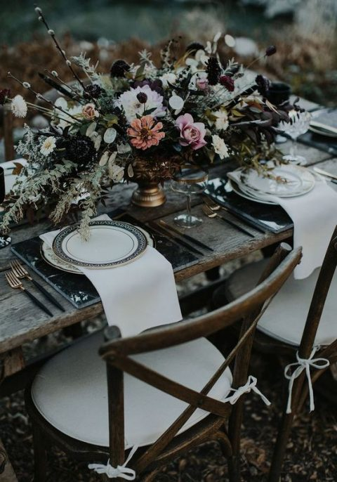 a dark ethereal wedding tablescape with lush florals and black marble chargers