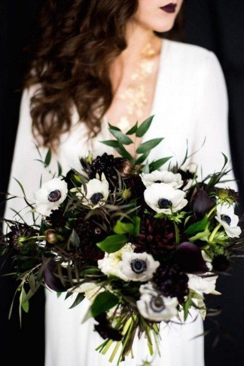 a dark moody wedding bouquet with very deep purple blooms
