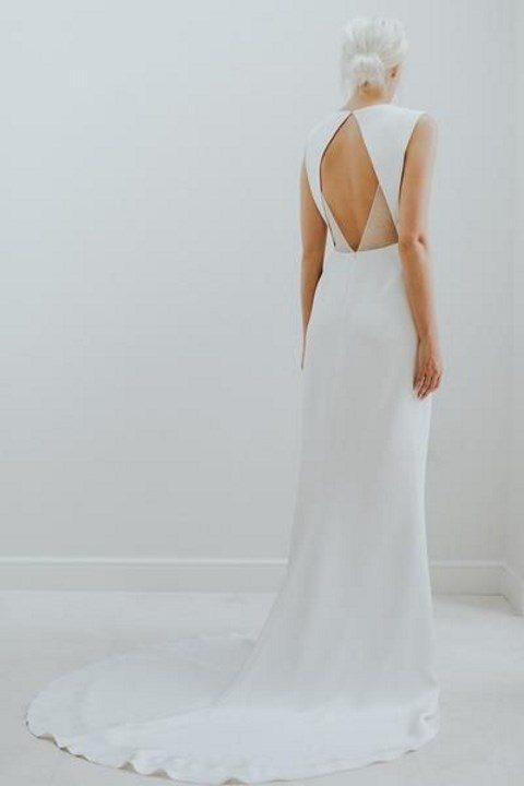 a gorgeous minimalist gown with a cutout back and sheer detailing, a train