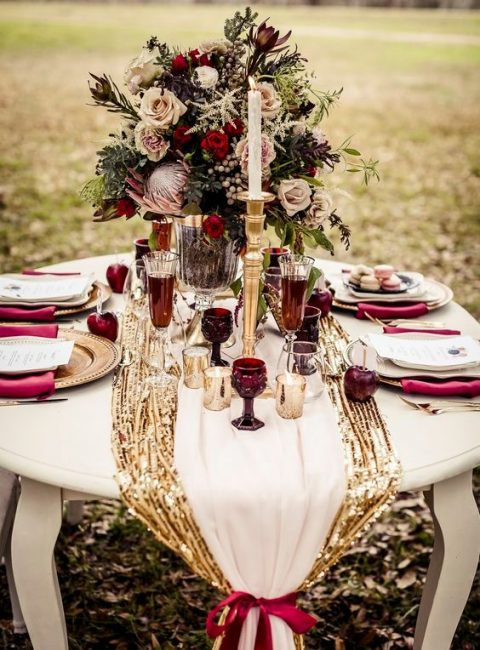 a holiday table runner of gold sequins and a neutral one on it, a plum-colored bow