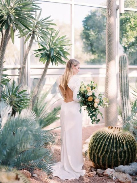 a long sleeve modern wedding dress with a cutout back and a small train