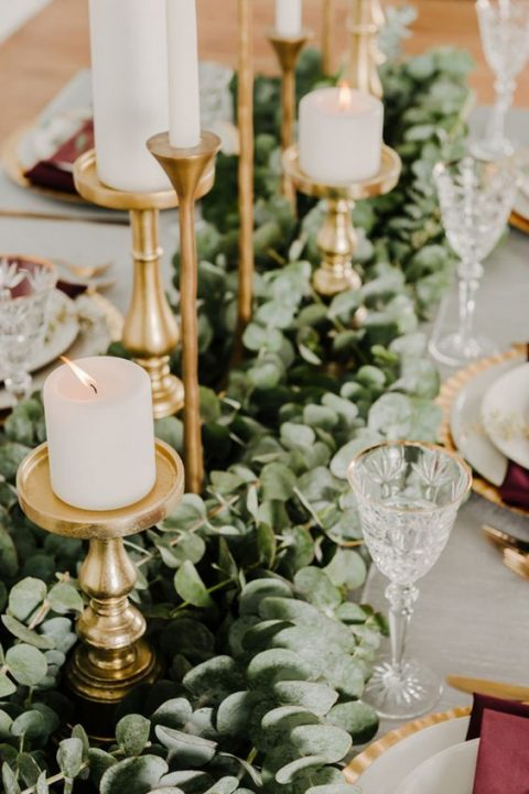a lush eucalyptus table runner with gilded candle holders and white candles