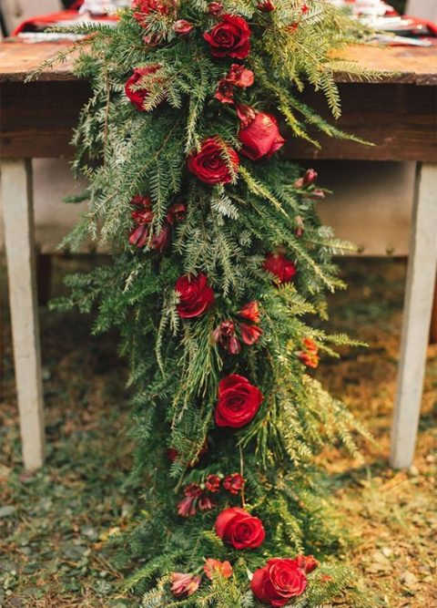 a lush evergreen table runner with red roses for a rustic wedding