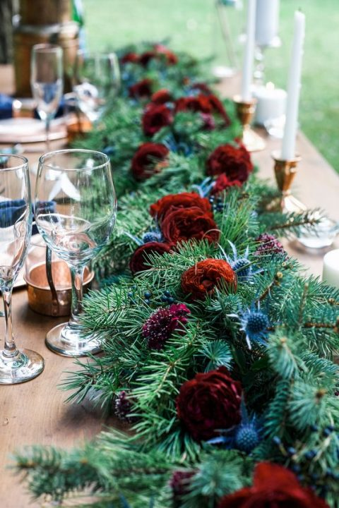 a lush evergreen table runner with thistles, berries and red roses