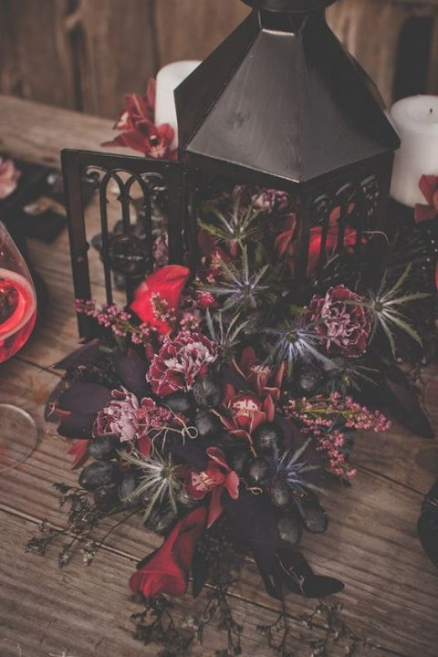 a lush floral centerpiece with a black lantern_ pink and purple blooms and thistles