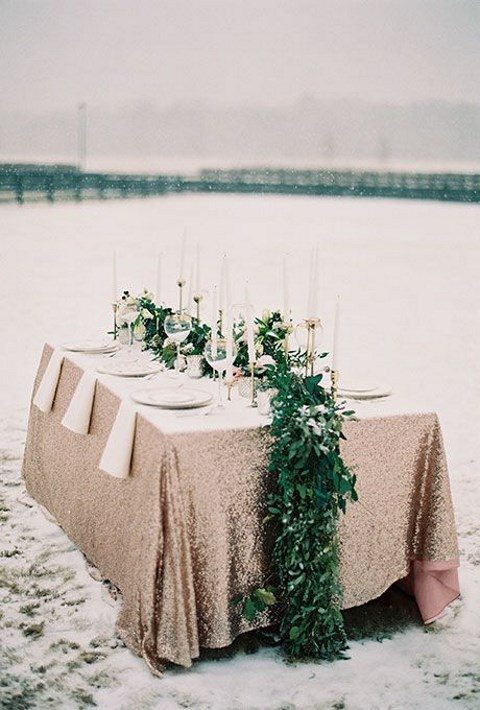 a lush greenery table runner over a copper sequin tablecloth
