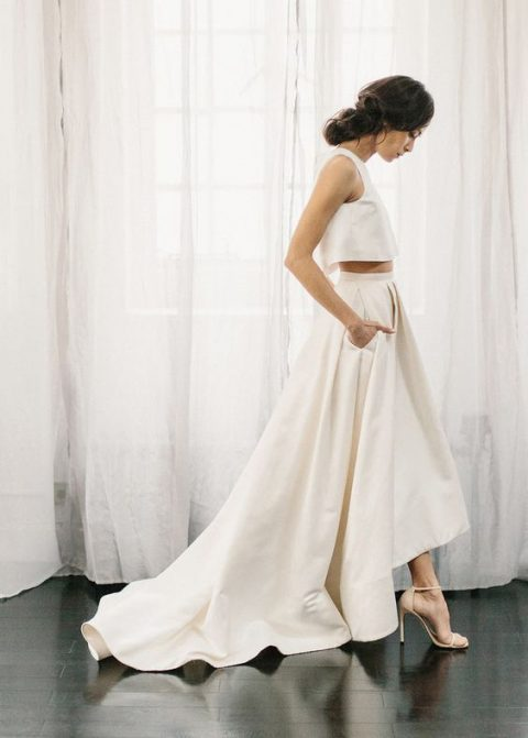 a minimalist two-piece wedding dress with a crop top and a high low skirt with a train