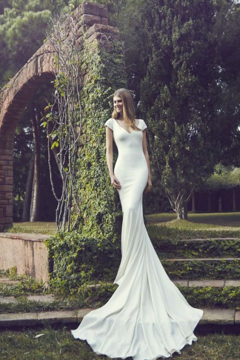 a minimalist wedding dress with cap sleeves, a deep V-neckline and a train