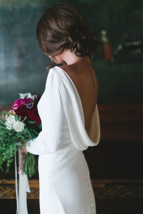a minimalist wedding dress with long sleeves, an open back and a row of buttons
