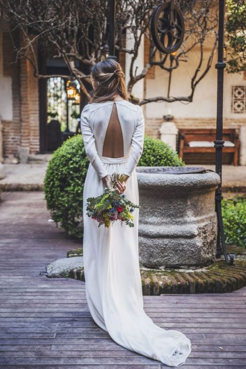 a minimalist wedding gown with textural seams and a cutout back