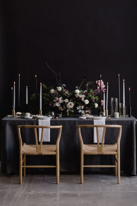 a modern moody tablescape with lush dark florals_ black and white candles and gilded touches