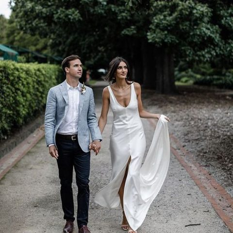 a modern strap wedding dress with a deep V-neckline and a front slit
