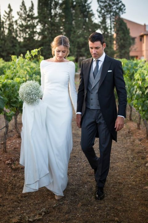 a modest wedding dress with long sleeves and a train, a bateau neckline