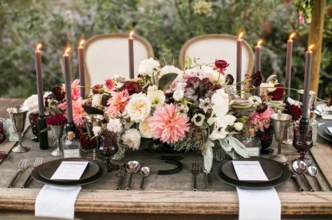 a moody rustic table setting with dark candles_ matte black plates and various blooms