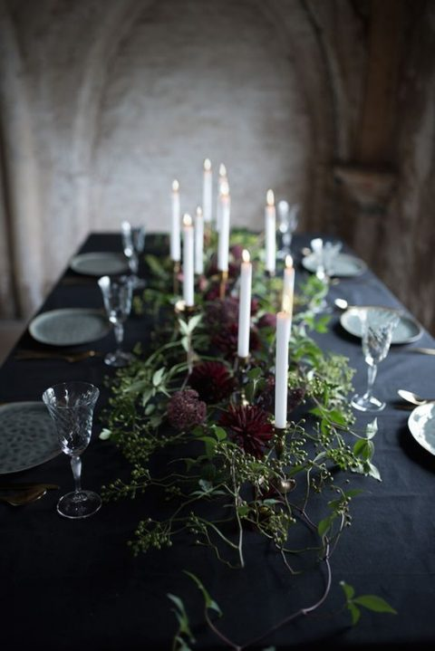a moody table setting with greenery_ burgundy blooms and grey plates