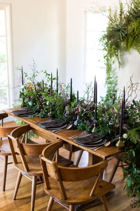 a moody table setting with lush greenery_ black candles_ black matte plates and glasses