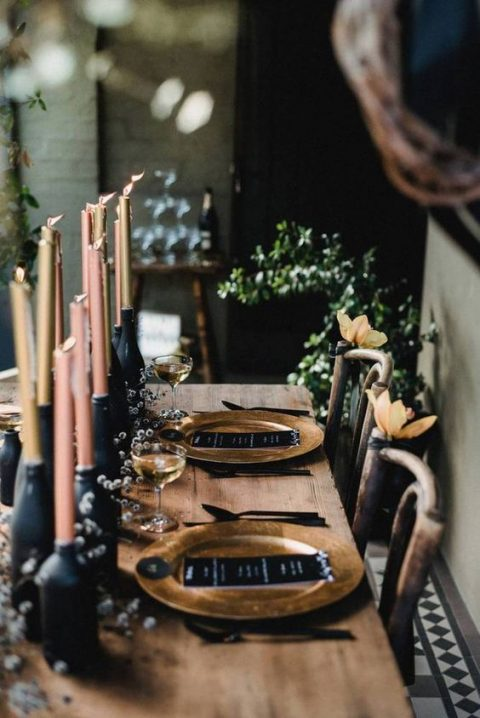 a moody tablescape with chalkboard bottles_ pastel candles_ gold chargers and black menus
