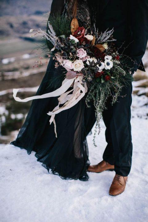 a moody wedding bouquet with dark florals_ evergreens_ dusty pink roses and ivory ribbons