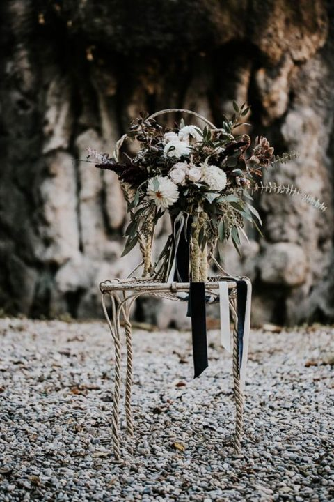 a moody wedding bouquet with white_ dark burgundy and greenery