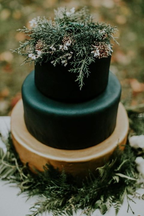 a moody winter wedding cake with a gold and matte black layers