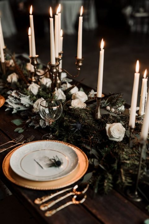 a moody winter wedding table with an evergreen runner_ white roses_ white candles and gold chargers
