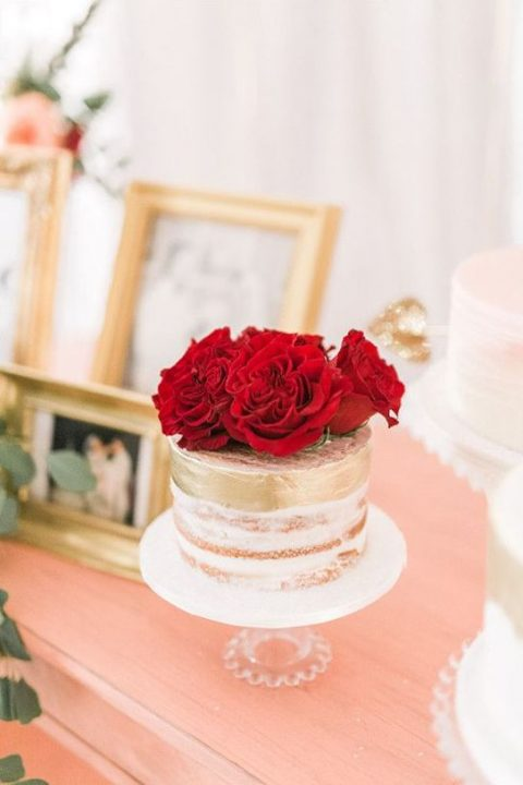 a naked wedding cake with gold touches and fresh red blooms on top