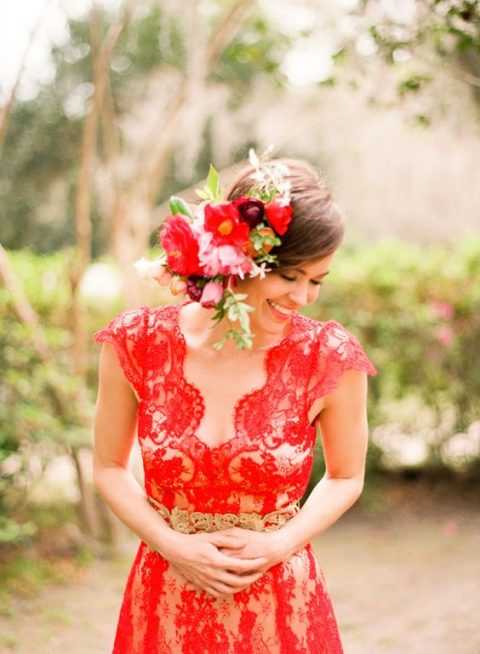 a red lace dress with wide straps and lush red blooms in the bridal hair