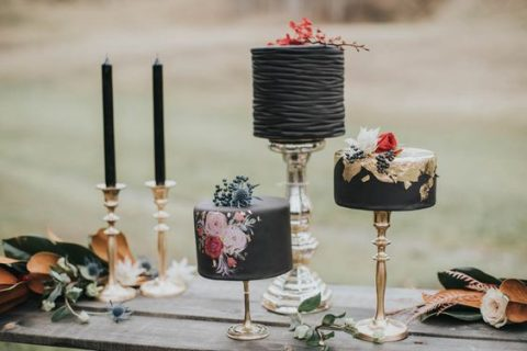 a refined moody wedding cake selection with gilded stands and black candles