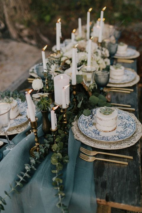 a slate blue ethereal table runner with eucalyptus and lots of candles for a winter coastal wedding