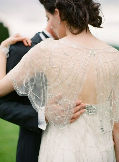 an embroidered and embellished capelet with a button on the back