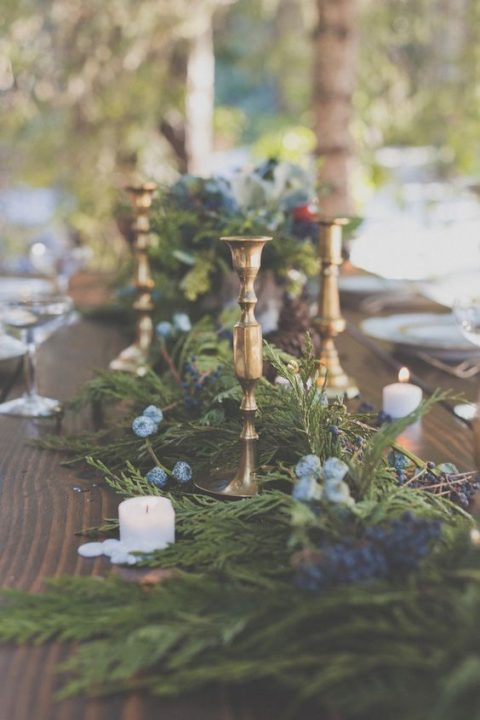 an evergreen table runner with blue flowers, berries and candles