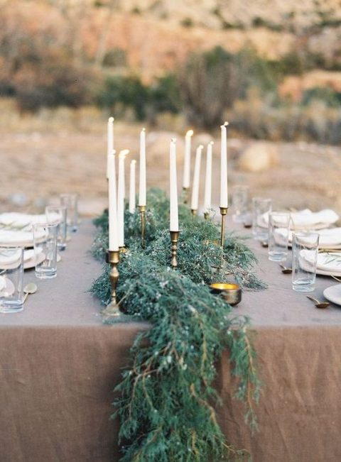 an evergreen table runner with candles