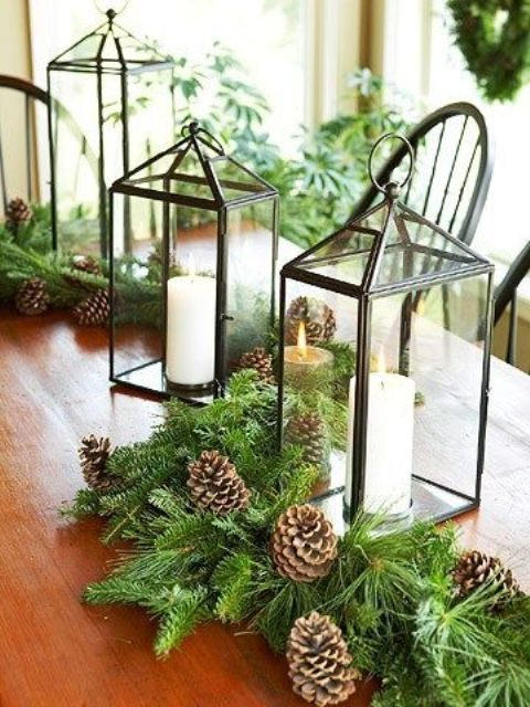 an evergreen table runner with pincones and candle lanterns