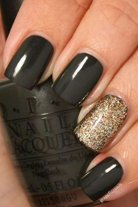 black nails with a gold accent nail