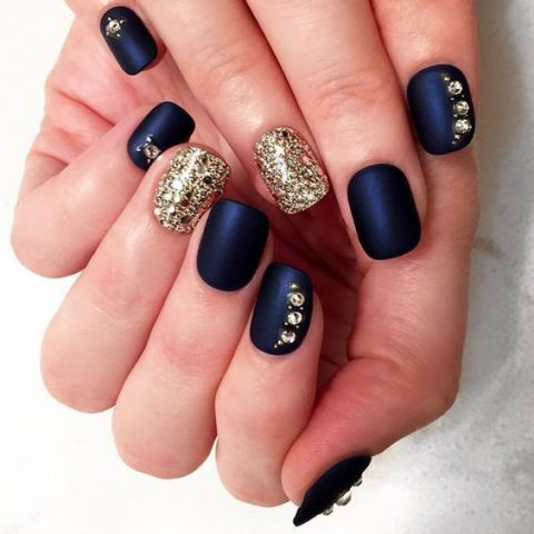 matte navy nails with rhinestones and gold glitter accent nails