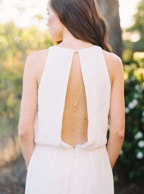 modern wedding gown with a cutout back on a pearl button and a back necklace