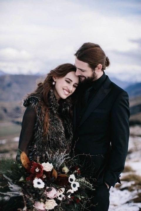 the bride wearing a dark faux fur vest_ a groom in black