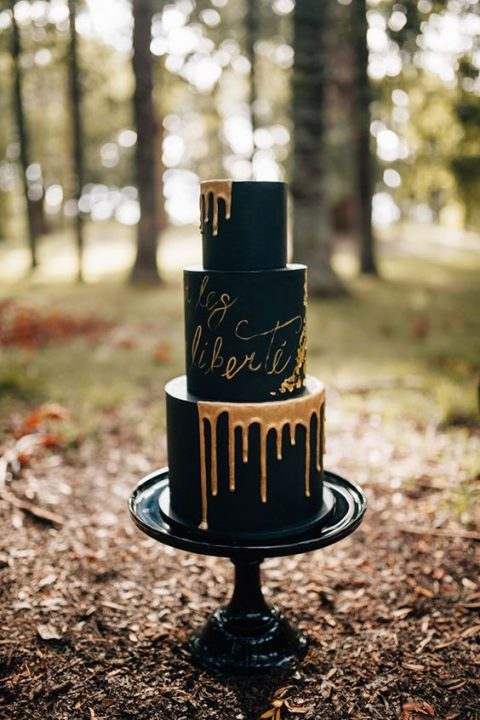 a black wedding cake with caramel dripping and letters